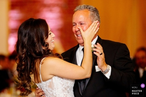 Chino Hills, Ca destination wedding reception photograph of bride wiping tears for dad while dancing with him