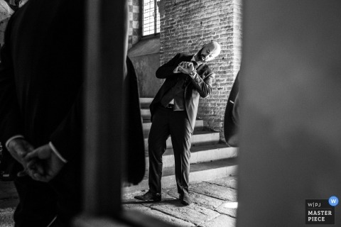 toscana wedding photograph of checking the time on a watch inside the church | before the ceremony starts