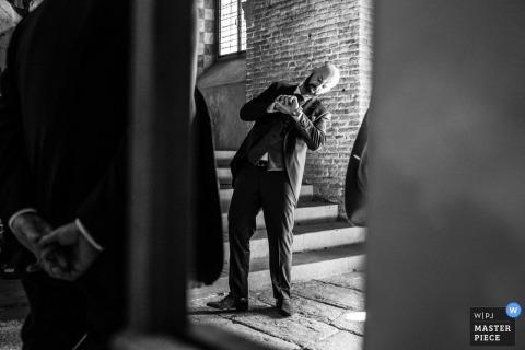 toscana - Hochzeitsfoto zur Überprüfung der Uhrzeit auf einer Uhr in der Kirche bevor die Zeremonie beginnt