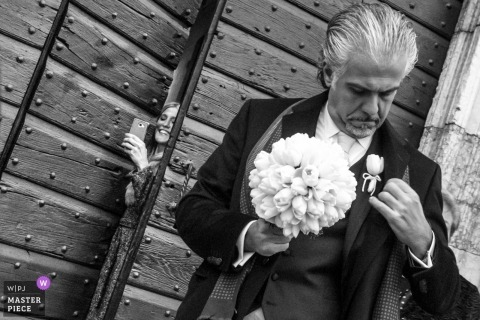 Mantova-Hochzeitsfotografie des Mannes mit Blumenstrauß außerhalb der Kirche vor der Zeremonie
