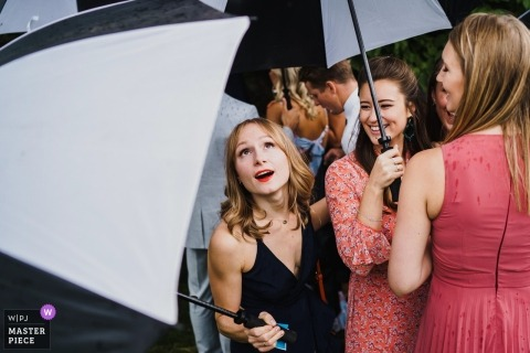 Wedding reception photography of guests with umbrellas in the rain | Norfolk weddings