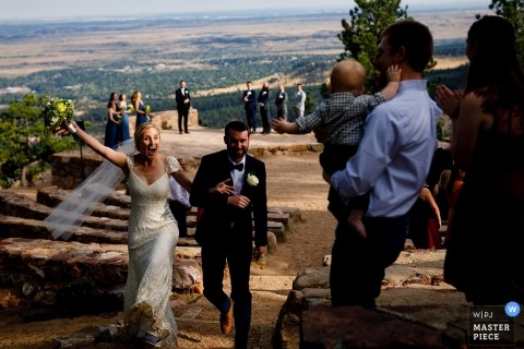wedding photography of elated bride and groom in Boulder, Colorado | walking out after the ceremony