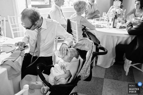 Elternschaft während der Hochzeitsfeier mit einem Baby und einer Flasche in Italien die harte Arbeit der Elternschaft bei Hochzeiten