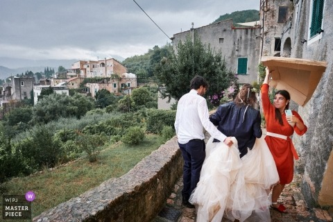 rainy day wedding in Savona | bridesmaid offering shelter from the rain for the bride