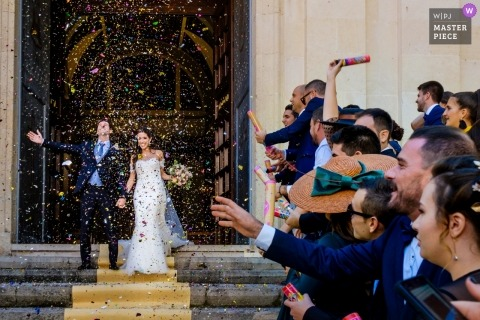 Alcoy wedding photograph of bride and groom leaving church to confetting and flower petals | capturing wedding moments at the church