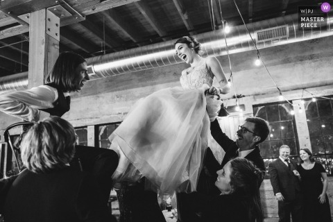 Wedding reception picture of bride and groom lifted in chairs by Seattle, Washington wedding photographer