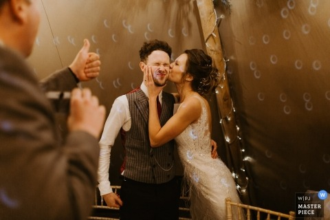 Los Angeles, Ca destination wedding reception photograph of bride kissing groom on the cheek to a thumbs-up responding guest