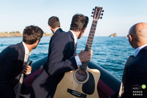 Lyon wedding photograph of groomsmen taking boat ride with guitar - Best French wedding photographer