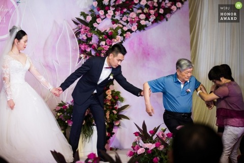 Wedding shoot during ceremony on stage with Tianjin couple helping parents