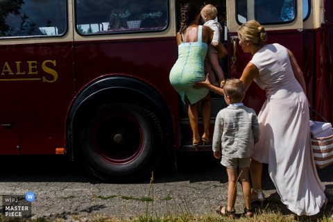 Flanders wedding photograph of bride helping friend into the bridal party bus