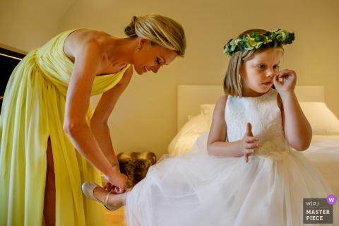 Flanders wedding photographer captured this flower girl getting her shoes put on | before the ceremony at a Belgium wedding