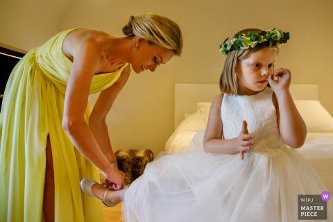 Fotograf ślubny Flandrii uchwycił dziewczynę z kwiatami, która wkładała buty | przed ceremonią na weselu w Belgii
