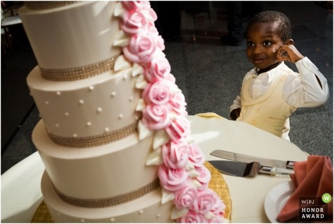 Chicago wedding photograph of ring bearer with a Sweet Tooth, looking at the cake