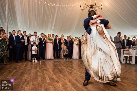 Panna młoda z naprawdę brudną suknią ślubną podnoszoną przez pana młodego na parkiecie wewnątrz recepcji namiotowej | Crossed Keys Inn | Fotografia ślubna New Jersey