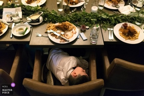 Chicago, Illinois wedding reception photo of young boy asleep at table with food
