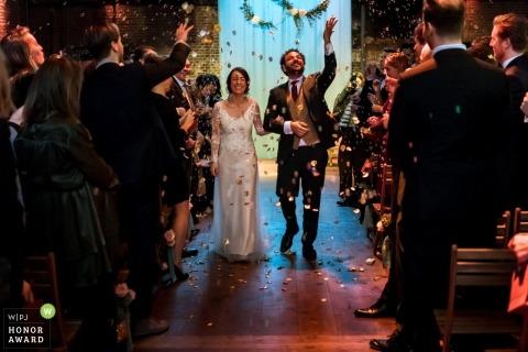 Zuid Holland-paar die door de douche van ceremonieconfettien tijdens hun huwelijk lopen