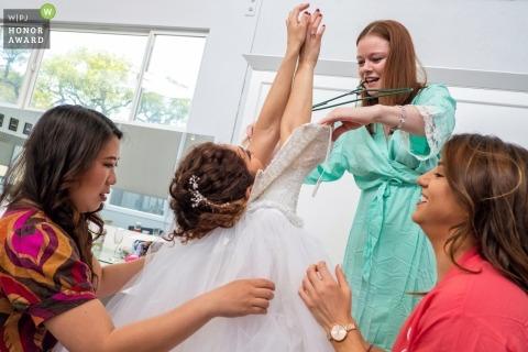 Hochzeits-Fotojournalismus in Malibu, Kalifornien | Braut, die in ihr Kleid geholfen wird