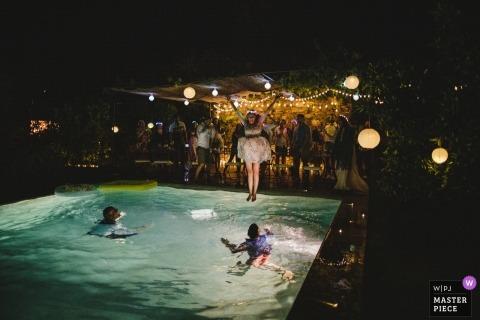 Porto, Portugal, photographie de réception de mariage à destination de la mariée qui saute dans la piscine avec la robe de mariée toujours