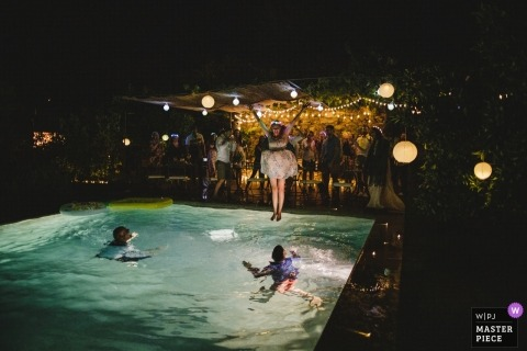 Porto, Portugal destination wedding reception photograph of bride jumping into pool with wedding dress still on