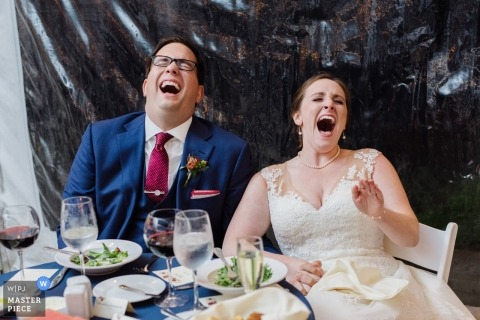 Wedding reception photography of bride and groom at head table laughing in Media, PA