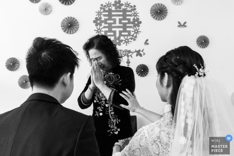 Wedding photograph of crying mom with bride and groom from Guangdong