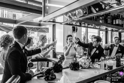 Prim and Proper, Detroit, MI | wedding reception photograph of bride toasting bridal party at the bar