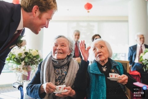 Wedding tea ceremony. Two elder matriarchs give advice to the groom | International Wedding photojournalist based in Oakland, CA