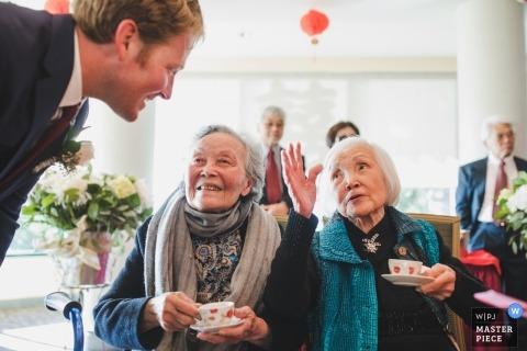 Cérémonie du thé de mariage. Deux matriarches âgées donnent des conseils au marié | Photojournaliste de mariage internationale basée à Oakland, Californie