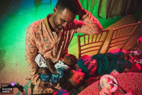 Réception de mariage à Aruba. Le père est assis avec deux enfants qui dorment sur ses genoux. Un moment précieux.