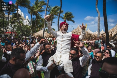 International Wedding photojournalist based in Oakland, CA | Indian wedding in Aruba. Groom is carried by his groomsmen during the Baraat on their way to the ceremony at Eagle Beach.