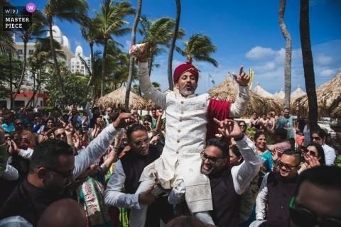 Fotoreporter di matrimoni internazionali con sede a Oakland, CA | Matrimonio indiano ad Aruba. Lo sposo è portato dai suoi testimoni dello sposo durante il Baraat mentre si recavano alla cerimonia a Eagle Beach.
