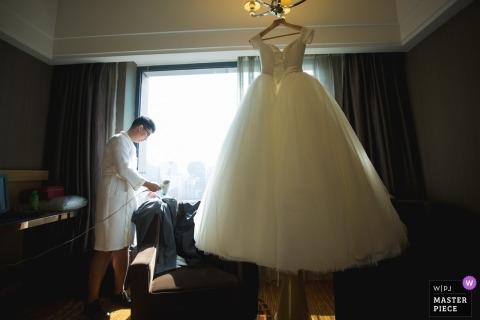 Fujian wedding photography of groom drying pants during getting ready with wedding gown hanging | China weddings