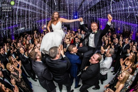 Royal Sonesta Hotel, Boston, MA wedding photojournalism image of a couple lifted above guests on dance floor