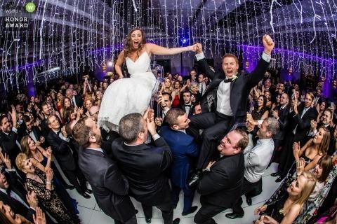 Royal Sonesta Hotel, Boston, MA bruiloft fotojournalistiek beeld van een paar opgeheven gasten boven op de dansvloer