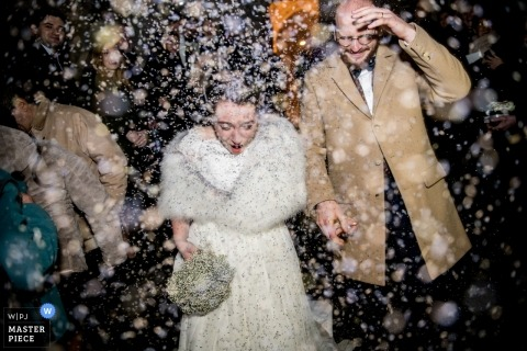 Wedding photograph of bride and groom leaving in snow shower | Wedding day moments captured in Oise