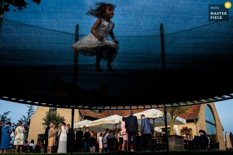 East Flanders wedding reception photograph of flowergirl jumping on trampoline