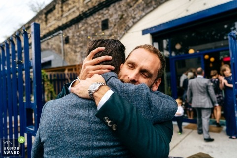 Arch Rivals, London Documentary wedding photograph of groom hugging