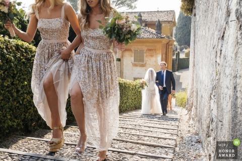 Villa Pizzo, Cernobbio, foto documental de la boda del lago Como de la novia, el papá y las damas de honor que suben los escalones