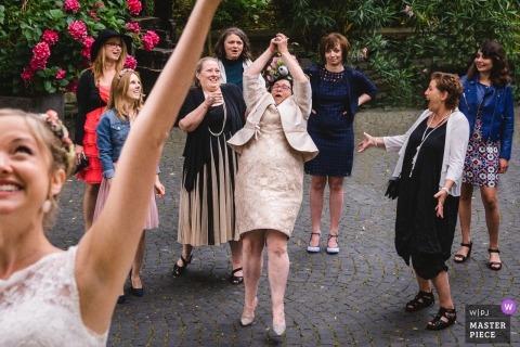 Frankfurter, hessischer Bestimmungsorthochzeitsempfang Foto des Gastes, der versucht, den Blumenstrauß der Braut zu fangen
