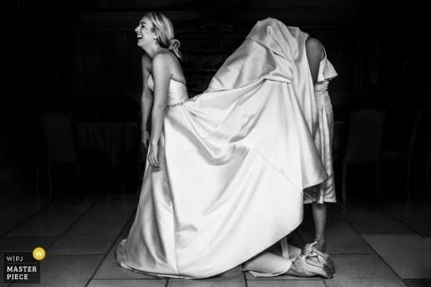Bride with helpers underneath her dress at a Devon, UK wedding