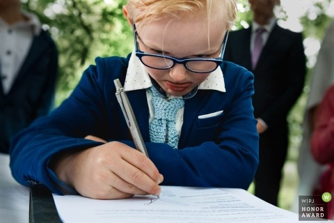 Wedding pictures of boy signing marriage certificate by Zuid Holland photographer