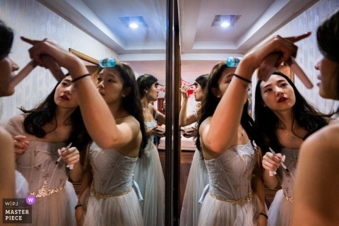 Wedding photograph of bride getting ready with friends in mirrors in Fujian, China
