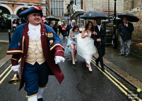 Photo de journalisme de mariage dans l'East Sussex représentant un couple RYE marchant dans la rue sous des parapluies sous la pluie