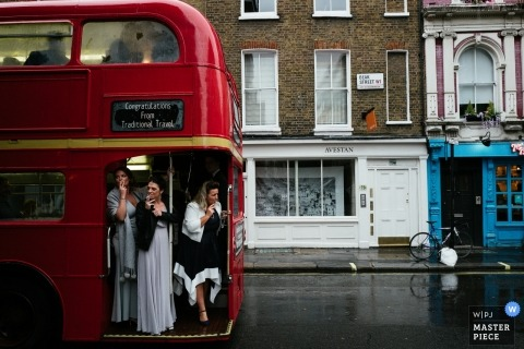 London wedding photograph of bridal party on a bus avoiding the rain | before the ceremony in England