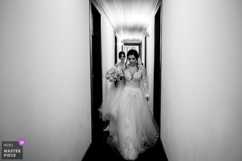 Wedding photograph of bride walking down hallway | Wedding day moments captured in Ouro Preto, Brazil