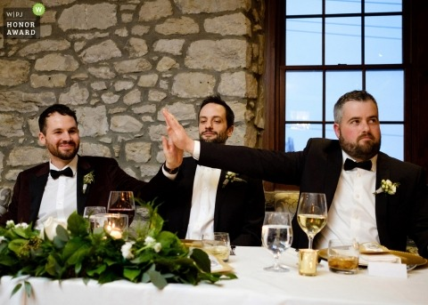 Toronto documentary wedding photo of groomsmen giving high five during speeches