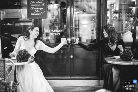 Wedding photograph of bride toasting at coffee shop with girlfriend | Wedding day moments captured in Paris, France