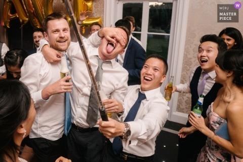 Botleys herenhuis, surrey, Engeland | Londense bruiloftsfotografie van jongens die selfie nemen bij de receptie