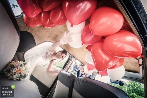 Wedding photo of couple entering limo with red balloons in Venice