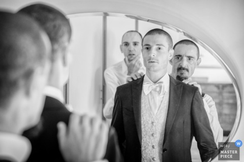 Venice wedding photography of groom getting help in the mirror before the ceremony